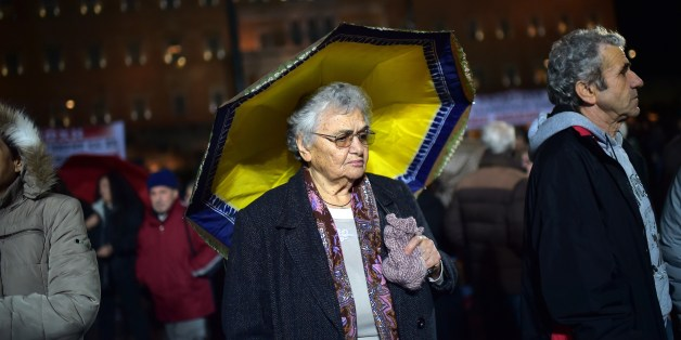 An elderly woman stands under a yellow umbrella outside the parliament in Athens on February 27, 2015 as supporters of the Communist Party of Greek (KKE) gather for an anti-government demonstration. AFP PHOTO / ARIS MESSINIS        (Photo credit should read ARIS MESSINIS/AFP/Getty Images)