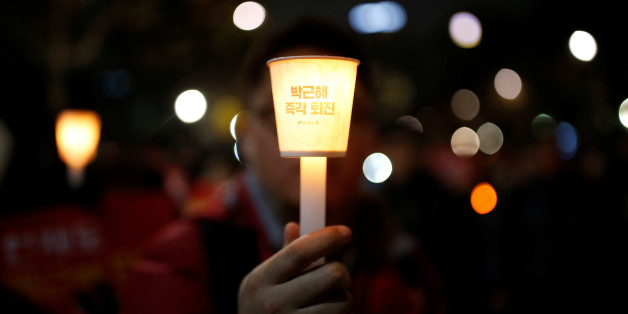 "A man holds a candlelight bearing a message that reads ""Step down Park Geun-hye immediately"" near the constitutional court during a protest demanding South Korean President Park Geun-hye's resignation in Seoul, South Korea December 17, 2016.   REUTERS/Kim Hong-Ji"