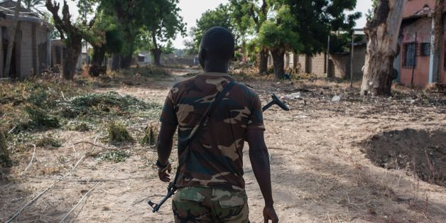A nigerian soldier patrols in the streets of Bama in northeast Nigeria on December 8, 2016. The houses are burnt-out shells, and charred cars and petrol pumps line the roads in the once-bustling Nigerian trade hub of Bama before it was razed by Boko Haram jihadists, know 85% is destroyed. The camp now houses a little over 10,000 people who either escaped or survived the seven months under Boko Haram rule. The conflict with Boko Haram in northeast Nigeria has displaced more than 2.6 million people. / AFP / STEFAN HEUNIS        (Photo credit should read STEFAN HEUNIS/AFP/Getty Images)