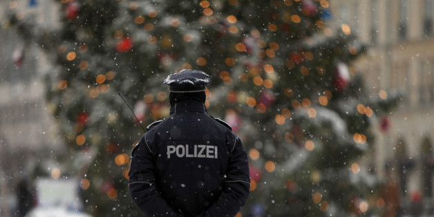 A police officer keeps watch near a Christmas tree during a snowy day in central Berlin, December 14, 2010.    REUTERS/Thomas Peter  (GERMANY - Tags: POLITICS ENVIRONMENT)