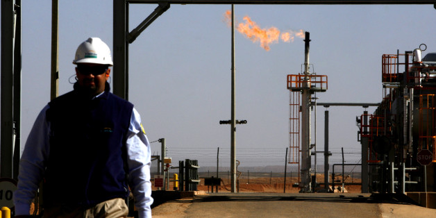 ALGERIA - DECEMBER 14:  An employee walks in front of a gas flare at the In Salah Gas (ISG) Krechba Project, run by Sonatrach, British Petroleum (BP), and StatoilHydro, in the Sahara desert near In Salah, Algeria, on Sunday, Dec. 14, 2008. From produced gas, the carbon capture plant, the largest and first of its kind, removes annually the carbon dioxide emissions equivalent of 200,000 automobiles running 30,000 kilometers. The CO2 is then reinjected into a two-kilometer deep reservoir instead of