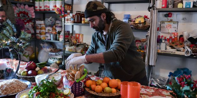 Chef Talal Rankoussi puts final touch to the prepared meal in the 'cafe Rits' in Ritsona refugee camp, some 80 km north of Athens on December 21, 2016.   Before braving a 'trip of death' to escape Syria, Talal Rankoussi was a chef in a Damascus restaurant considered the largest in the world.Bawabet Al Dimashq -- Damascus Gate -- still holds that distinction in the Guinness Book of Records as it can seat over 6,000 people.So when 41-year-old Talal was asked by a US benefactor to spice up the meal
