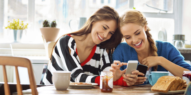 Two cheerful friends sitting at the kitchen table and using smart phones.