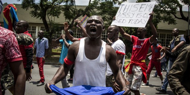 A Congolese protester holds a book of the DRC's constitution in defiance against the President of the Democratic Republic of the Congo, Joseph Kabila, at a protest demanding him to step down on December 20, 2016 in Pretoria.
