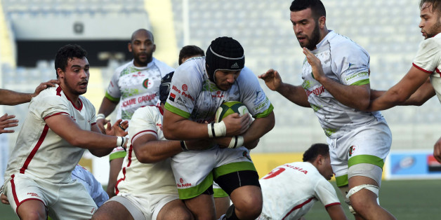 Algerian player (C) is tackled by Tunisian players during their friendly rugby match, Alegria's first international rugby match on home soil, on December 18, 2015 at the Stade Zabana in the Algerian coastal city of Oran. AFP PHOTO / FAROUK BATICHE / AFP / FAROUK BATICHE        (Photo credit should read FAROUK BATICHE/AFP/Getty Images)