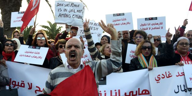 Tunisians shout slogans during a demonstration outside parliament against allowing Tunisians who joined the ranks of jihadist groups to return to the country, in the capital Tunis on December 24, 2016. The writing in Arabic reads: ''we are all under threat by terrorism''. / AFP / FETHI BELAID        (Photo credit should read FETHI BELAID/AFP/Getty Images)