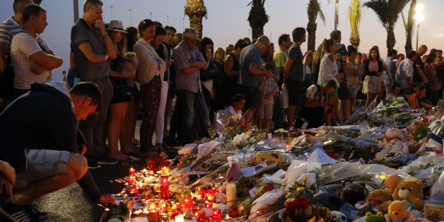 People gather around flowers and burning candles to pay tribute to victims of the truck attack along the Promenade des Anglais on Bastille Day that killed scores and injured as many in Nice, France, July 17, 2016.  REUTERS/Pascal Rossignol