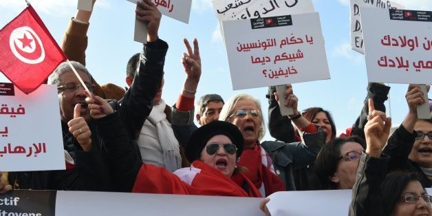 Tunisians shout slogans during a demonstration outside parliament against allowing Tunisians who joined the ranks of jihadist groups to return to the country, in the capital Tunis on December 24, 2016. The writing in Arabic reads: ''Tunisian leaders why are you so scared?'' / AFP / FETHI BELAID        (Photo credit should read FETHI BELAID/AFP/Getty Images)