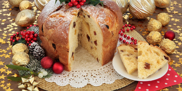 Panettone christams cake and slice with bauble decorations, holly and winter flora over oak background with stars.