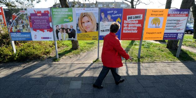 Eine Frau geht an Wahlplakaten vorbei