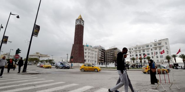 A photo taken on November 10, 2016 shows Tunisians walking past the Great Clock in the Habib Bourguiba avenue in the capital Tunis. A Tunisian man climbed the Great Clock of the Habib Bourguiba avenue of the capital, early in the morning, and was ready to jump into the void in protest against the election of Donald Trump as the President of the United States.  / AFP / FETHI BELAID        (Photo credit should read FETHI BELAID/AFP/Getty Images)