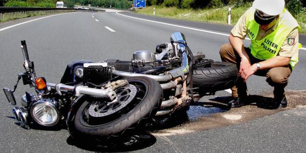 Ein Polizist begutachtet das Motorrad eines tödlich verunglückten Fahrers auf der Autobahn 45 bei Siegen