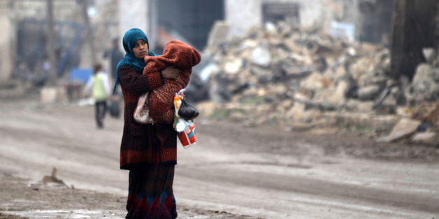A woman carries a child as she walks near rubble of damaged buildings in al-Rai town, northern Aleppo countryside, Syria December 25, 2016. REUTERS/Khalil Ashawi