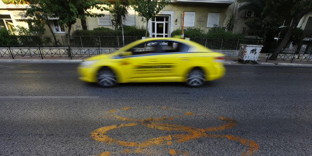 A taxi drives by fading Olympic rings which mark the Olympic Traffic Lane on an avenue leading to the Athens 2004 Olympic Complex in Athens July 26, 2014. Ten years after Greece hosted the world's greatest sporting extravaganza, many of its once-gleaming Olympic venues have been abandoned while others are used occasionally for non-sporting events such as conferences and weddings. For many Greeks who swelled with pride at the time, the Olympics are now a source of anger as the country struggles through a six-year depression, record unemployment, homelessness and poverty. Just days before the anniversary of the Aug. 13-29 Games in 2004, many question how Greece, among the smallest countries to ever host the Games, has benefited from the multi-billion dollar event. Picture taken July 26, 2014. REUTERS/Yannis Behrakis (GREECE - Tags: BUSINESS POLITICS SPORT TRANSPORT)