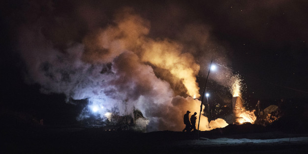 INNER MONGOLIA, CHINA - NOVEMBER 03:Chinese labourers walk as smoke and steam rises at a cooling pit and furnace at an unauthorized steel factory on November 3, 2016 in Inner Mongolia, China. To meet China's targets to slash emissions of carbon dioxide, authorities are pushing to shut down privately owned steel, coal, and other high-polluting factories scattered across rural areas. In many cases, factory owners say they pay informal 'fines' to local inspectors and then re-open. The enforcement comes as the future of U.S. support for the 2015 Paris Agreement is in question, leaving China poised as an unlikely leader in the international effort against climate change. U.S. president-elect Donald Trump has sent mixed signals about whether he will withdraw the U.S. from commitments to curb greenhouse gases that, according to scientists, are causing the earth's temperature to rise. Trump once declared that the concept of global warming was 'created' by China in order to hurt U.S. manufacturing. China's leadership has stated that any change in U.S. climate policy will not affect its commitment to implement the climate action plan. While the world's biggest polluter, China is also a global leader in establishing renewable energy sources such as wind and solar power. (Photo by Kevin Frayer/Getty Images)