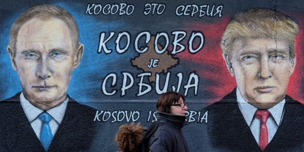 """A woman with a child walks past a mural of U.S. president-elect Donald Trump and Russian President Vladimir Putin in Belgrade, Serbia, December 4, 2016. The text on the mural reads in Russian, Serbia and English """"Kosovo is Serbia"""".  REUTERS/Marko Djurica"""