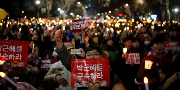 "People march toward the constitutional court during a protest demanding South Korean President Park Geun-hye's resignation in Seoul, South Korea December 17, 2016. The sign reads ""Arrest Park Geun-hye"".   REUTERS/Kim Hong-Ji"