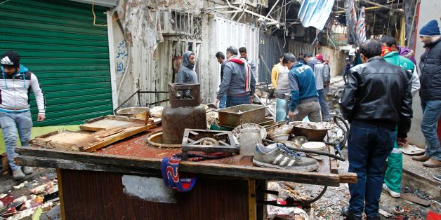 Iraqis look at the aftermath following a double bomb attack in a busy market area in Baghdad's central al-Sinek neighbourhood on December 31, 2016. Baghdad has been on high alert since the start on October 17 of an offensive, Iraq's largest military operation in years, to retake the northern jihadist stronghold of Mosul / AFP / SABAH ARAR        (Photo credit should read SABAH ARAR/AFP/Getty Images)