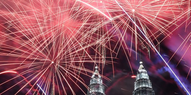 Fireworks illuminate the sky near Malaysia's Petronas Twin Towers during New Year celebrations in Kuala Lumpur on January 1, 2017. / AFP / MOHD RASFAN        (Photo credit should read MOHD RASFAN/AFP/Getty Images)