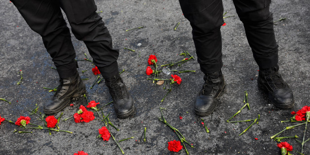 Flowers are placed next to Turkish police officers as they stand guard near the Reina nightclub, which was attacked by a gunman, in Istanbul, Turkey, January 1, 2017.    REUTERS/Umit Bektas
