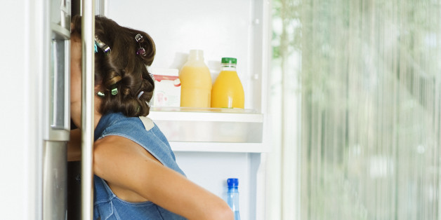 Profile of a young woman 25 years old having curlers in hair, wearing high heels and blue short dress, she is kneeling and searching for food with head into her opened refrigerator, luminous interior, France, Alpes Maritimes, Nice