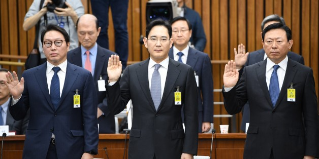 (L-R) SK Group chairman Chey Tae-Won, Samsung Group's heir-apparent Lee Jae-Yong and Lotte Group Chairman Shin Dong-Bin take an oath during a parliamentary probe into a scandal engulfing President Park Geun-Hye at the National Assembly in Seoul on December 6, 2016. The publicity-shy heads of South Korea's largest conglomerates faced their worst nightmare on December 6, as they were publicly grilled about possible corrupt practises before an audience of millions. / AFP / POOL / JUNG YEON-JE