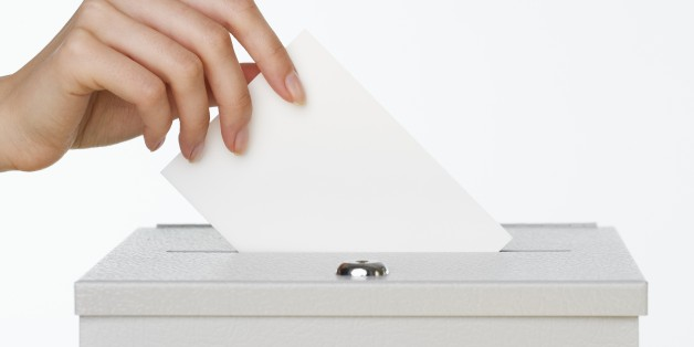Close up of woman's hand putting card in box with slot