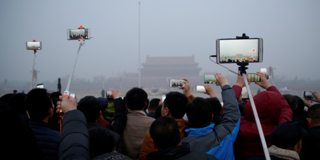 People take videos of a flag-raising ceremony during smog at Tiananmen Square after a red alert was issued for heavy air pollution in Beijing, China, December 20, 2016. REUTERS/Jason Lee
