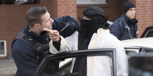 Ein vermummter Mann verlässt in Begleitung von Polizisten eine Moschee in Berlin