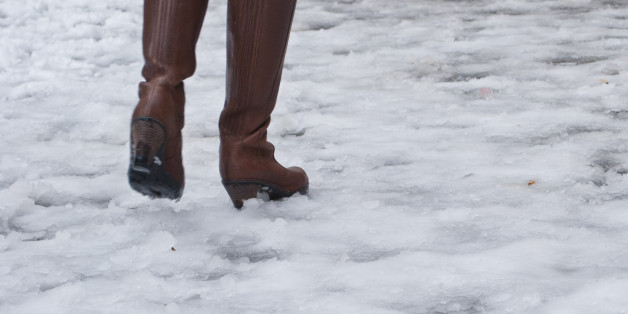 Woman with brown leather boots walks on icy street in Rome