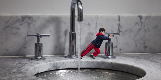 Miniature boy turning off water tap