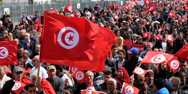 Tunisians wave their national flag and chant slogans during a march against extremism outside Tunis' Bardo Museum on March 29, 2015. Thousands of Tunisians set off for a march 'against terrorism' through the capital following the massacre of foreign tourists at the country's national museum. AFP PHOTO / FETHI BELAID        (Photo credit should read FETHI BELAID/AFP/Getty Images)
