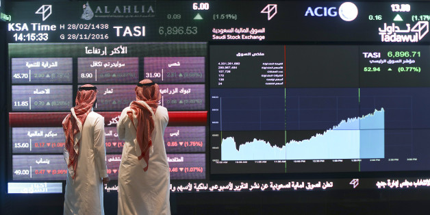 Visitors stand and watch stock movements displayed on large video screens inside the Saudi Stock Exchange, also known as the Tadawul All Share Index in Riyadh, Saudi Arabia, on Monday, Nov.28, 2016. The Tadawul All Share Index advanced 26 percent since Saudi Arabias record-breaking bond sale last month, the most in the world during that period. Photographer: Simon Dawson/Bloomberg via Getty Images