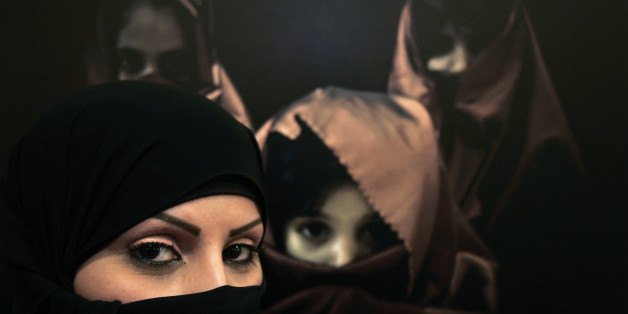 Saudi photographer Muneera Al Romaih poses in front of one of her photographs during the opening of a gallery by a group of Saudi women photographers in Amman April 8, 2009.  REUTERS/Muhammad Hamed (JORDAN SOCIETY)