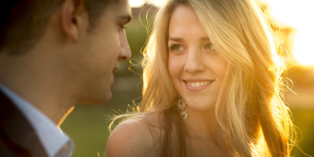 A pretty young girl stares at the eyes of a smart young man stands close to her.