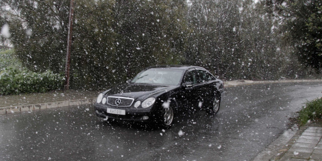 LARNACA, CYPRUS - 2015/02/19: A car passing by the snowing road in Nicosia, Cyprus. Due to bad weather conditions, snow was experienced for the first time since 1996 at Larnaca and other areas in Cyprus. (Photo by Yiorgos Doukanaris/Pacific Press/LightRocket via Getty Images)