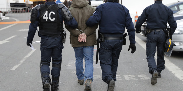 French police escort a man who was apprehended after farmers destroyed the French Ministry of Agriculture information booth on the opening day of the International Agricultural Show in Paris, France, February 27, 2016. French farmers protested during an early morning visit by France's President Hollande. The Paris Farm Show runs from February 27 to March 6, 2016. REUTERS/Benoit Tessier     ATTENTION EDITORS FRENCH LAW REQUIRES THAT HANDCUFFS OR RESTRAINTS ARE MASKED IN PUBLICATIONS WORLDWIDE