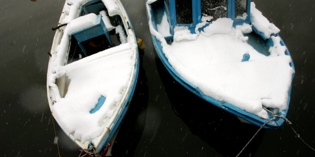Snow-covered fishing boats are docked at a marine in Chalkida town in Evia island, northeast of Athens, January 25, 2006. More than 400 villages and towns were cut off after 36 hours of continuous snowfall while hundreds of snow-clearing vehicles struggled to keep main routes open. Ports across Greece stayed shut as icy gale-force winds swept across the Aegean sea, dropping a carpet of snow over the islands. REUTERS/Yiorgos Karahalis