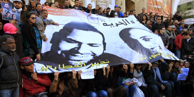 People pose around a poster of journalists Nadhir Ktari (L, in poster) and Sofiane Chourabi, who went missing in Libya in September, during a demonstration over their disappearance, in Tunis January 9, 2015.  REUTERS/Anis Mili (TUNISIA - Tags: CIVIL UNREST POLITICS CRIME LAW MEDIA)