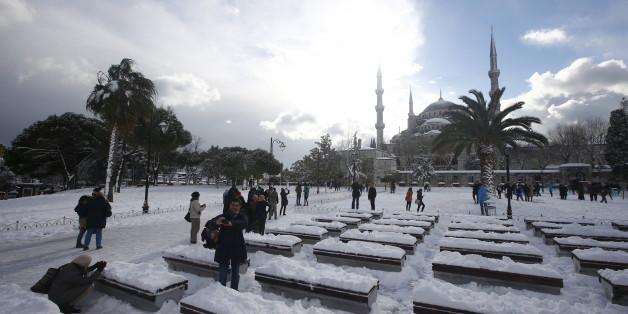 Tourists take a photo on the snow-covered Sultanahmet Square in the historic old town of Istanbul, Turkey,  December 31, 2015.  REUTERS/Osman Orsal