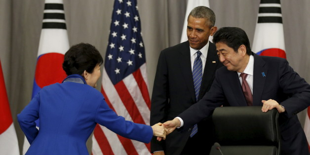 U.S. President Barack Obama stands behind as South Korean President Park Geun-Hye (L) and Japanese Prime Minister Shinzo Abe shake hands at the end of their trilateral meeting at the Nuclear Security Summit in Washington March 31, 2016.  REUTERS/Kevin Lamarque