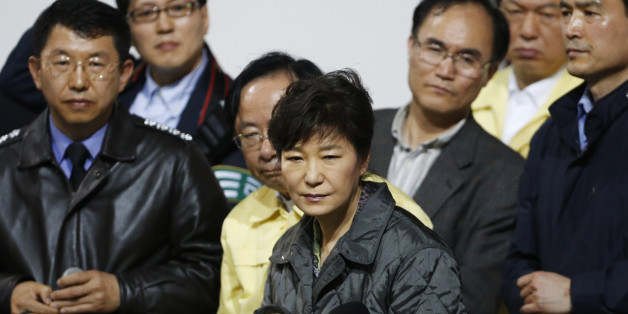 "South Korean President Park Geun-hye (C) listens to a family member of a missing passenger who was on South Korean ferry ""Sewol"", which sank at the sea off Jindo, during her visit to a gym where family members gathered, in Jindo April 17, 2014. Rescuers fought rising winds, strong waves and murky waters on Thursday as they searched for hundreds of people, mostly teenage schoolchildren, still missing after a South Korean ferry capsized more than 24 hours ago.   REUTERS/Kim Hong-Ji (SOUTH KOREA -"