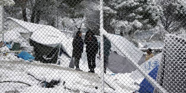 Migrants stand next to their tents at the Moria hotspot on the island of Lesbos , following heavy snowfalls on January 7, 2017. 