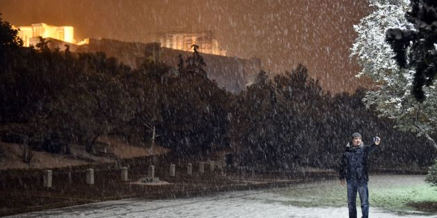 A man takes a selfie with the Acropolis in the background during heavy snowfall in central Athens on the night of January 9, 2017.