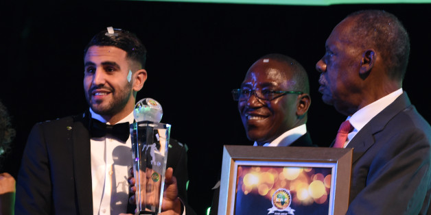 Algerian and Leicester forward Riyad Mahrez (L) receives trophy from Nigeria's sports minister Solomon Dalung (C) and CAF President Issa Hayatou after being crowned African Footballer of the Year in Abuja, on January 5, 2017.Algerian and Leicester striker Riyad Mahrez has been crowned the CAF African best Footballer for 2016 and beating former best player and Gabonese forward Pierre-Emerick  Aubameyang  and Sehegalese striker Sadio Mane, for the continent's most prestigious individual award. / A