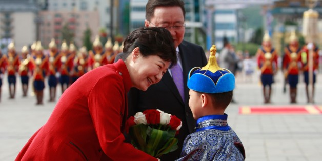 South Korea's President Park Geun-hye (L) is greeted by a Mongolian boy as Mongolia's President Tsakhiagiin Elbegdorj looks on during a welcoming ceremony for Park in Ulan Bator on July 17, 2016.Park is on a state visit to Mongolia after attending the 11th Asia-Europe Meeting (ASEM) summit. / AFP / BYAMBASUREN BYAMBA-OCHIR        (Photo credit should read BYAMBASUREN BYAMBA-OCHIR/AFP/Getty Images)