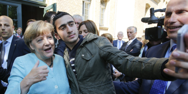 A migrant takes a selfie with German Chancellor Angela Merkel outside a refugee camp near the Federal Office for Migration and Refugees after registration at Berlin's Spandau district, Germany September 10, 2015. REUTERS/Fabrizio Bensch TPX IMAGES OF THE DAY