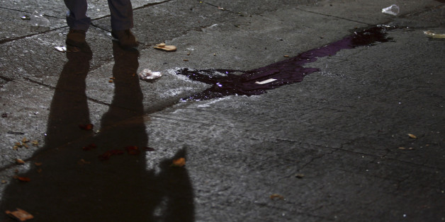 The shadow of a police officer is cast near a puddle of blood at a crime scene outside a nightclub in an upscale neighborhood of Guadalajara February 12, 2011. A group of hitmen showed up outside the club, started shooting and threw a grenade inside the building killing at least seven people and injuring another 30, according to local media. Cartel hitmen are murdering rivals and terrifying residents across Mexico's second city Guadalajara as it prepares to host the Pan American Games in a deepening of the country's drugs war. REUTERS/Alejandro Acosta (MEXICO - Tags: CRIME LAW CIVIL UNREST)