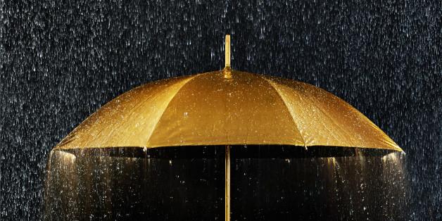 Conceptual photograph of a golden umbrella with rain.
