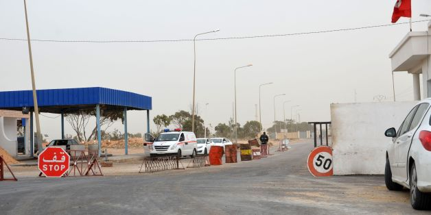 A picture taken on March 22, 2016 shows vehicles waiting near the Tunisian customs post at the Ras Jedir border crossing with Libya, south of the town of Ben Guerdane, after it was reopened after a two-week closure in response to a deadly jihadist attack on a town near the frontier. 
